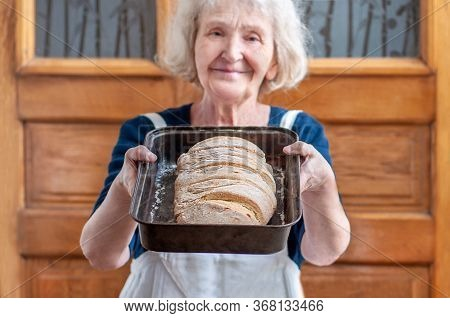 Elderly Grandmother Bakes Bread At Home On Quarantine Covid-19. A Good Housewife With Homemade Bread
