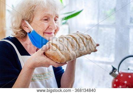 Elderly Woman In Protective Mask Sniffs Baked Homemade Bread In The Kitchen. Quarantine Coronavirus