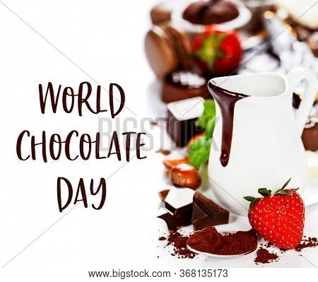 World Chocolate Day concept - 7 july. Delicious rich and thick chocolate sauce in a jug and assorted chocolates - food and drink