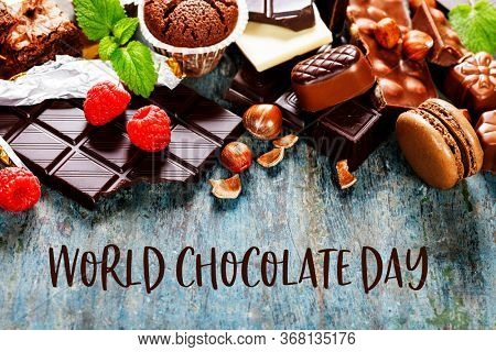 World Chocolate Day concept. An assortment of white, dark, and milk chocolate with nuts, muffins, macaroons - on wooden background