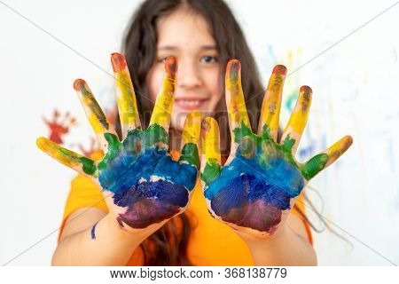 Portrait Of A Girl With Multi-colored Palms. The Babys Face Is Out Of Focus. Rainbow On The Hands. T