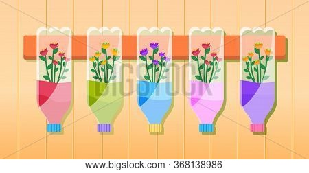 Multi-colored Flowers In Bottles Hang On A Wooden Plank On The Wall. Reuse Plastic Bottle As Flower