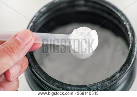 L-glutamine Supplement. Man Holding Scoop With L-glutamine Powder Inside. Close Up.