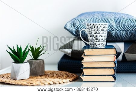 Cozy Home Interior Decor: White And Black Cup, Stack Of Books, Plants In Pots On A Wicker Stand, Blu