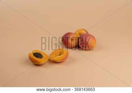 Whole Apricots And One Sliced Apricot On A Peachy Colored Background. Summer Fruit, Healthy Eating,