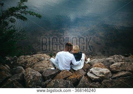 Interracial Couple Sits On Rocks And Hugs Against Background Of River. Concept Of Love Relationships