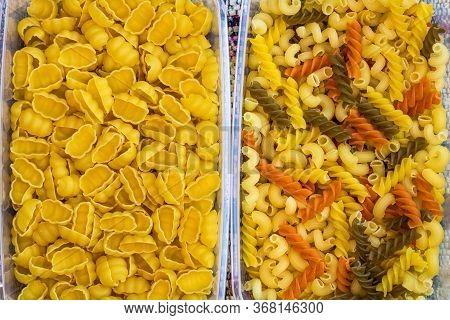 Different Types Of Raw Italian Pasta (gnocchi, Tricolor Pasta) In Plastic Transparent Containers.