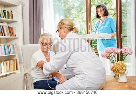 The doctor and the geriatric nurse take care of the elderly in the senior residence