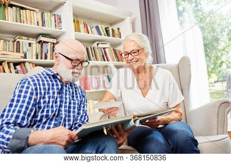 Couple of retired seniors together looking at photos in the senior citizen apartment