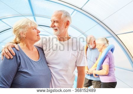 Amorous senior couple with friends at aqua fitness as a health sport
