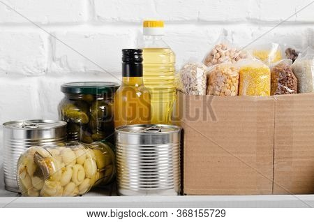 Set Of Uncooked Foods On Pantry Shelf Prepared For Disaster Emergency Conditions On Brick Wall Backg