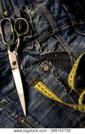 Tailoring And Design Concept. Scissors, Measuring Tape And Ripped Jeans. Old Metal Scissors And A Ye