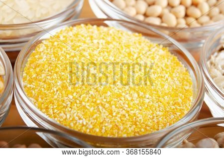 Corn Grits Closeup In Glass Bowl On Wooden Kitchen Table, Non-perishable, Long Shelf Life Food Conce