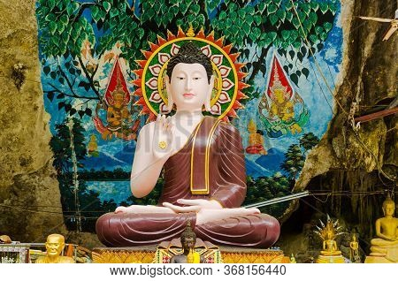 Figure Of Sitting Buddha With Golden Aura And Wall Paintings In Tiger Cave Temple, Thailand.