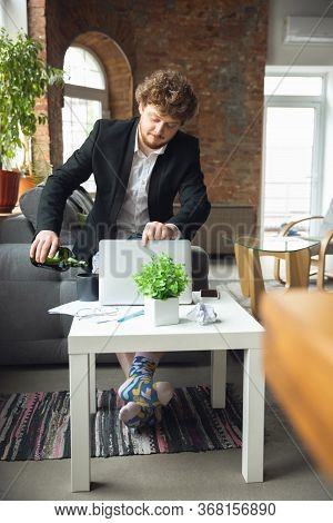 Drinking Alcohol. Man Without Pants But In Jacket Working On A Computer, Laptop. Remote Office Durin