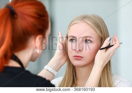 Makeup Artist Looks At Symmetry Models Eyebrows. During Healing Process, Loss Color Is Minimal. Girl