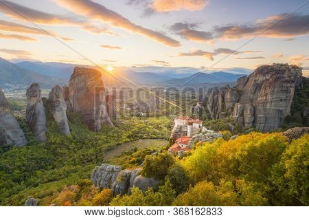 Landscape of Meteora, Greece at romantic sundown time with real sun and sunset sky. Meteora - incredible sandstone rock formations.  The Meteora area is on UNESCO World Heritage