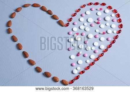 Healthy Eating Concept. Crooked Heart Made From Pills And Almonds. Healthy Fats And Red And White Pi
