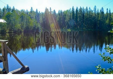 Forest Landscape Of A Lake With Blue, Calm Water On A Clear, Sunny Day. The Green Forest Around The