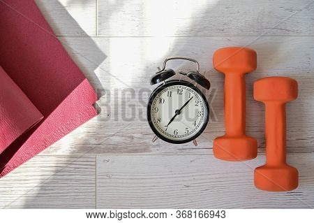 Top View On Orange Dumbbell Alarm Clock And Raspberry Yoga Mat. The Concept Of Home Sports During Qu