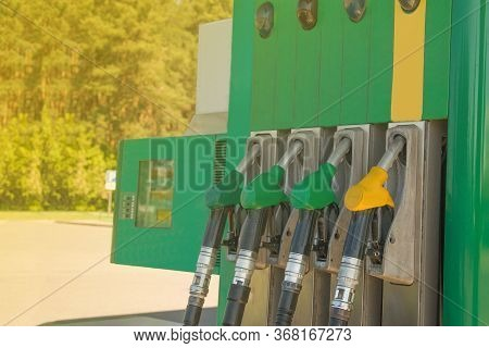 Gas Station With The Rays Of The Sun. Colorful Petrol Pump Filling Nozzles. Fuel Oil Gasoline Dispen