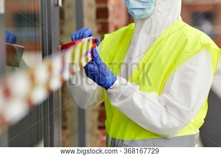 quarantine and pandemic concept - healthcare worker in protective gear or hazmat suit, medical mask and gloves enclosing building with caution tape outdoors