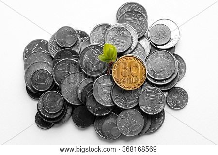Stack Of Euro And Hryvnia  Cent Coins On A White Background. Strengthening The National Currency Of
