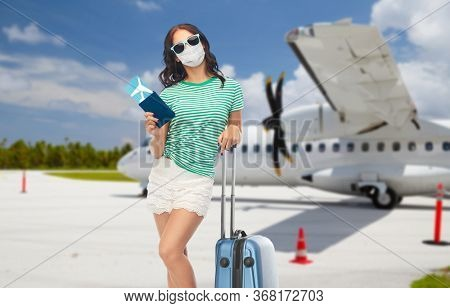 tourism, pandemic and health care concept - teenage girl in sunglasses wearing face protective medical mask with travel bag and air ticket over plane on airfield background