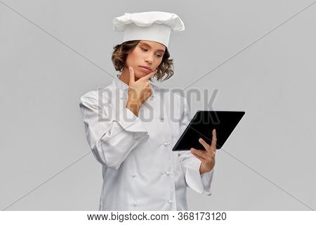 cooking, culinary and people concept -thinking female chef in toque with tablet pc computer over grey background