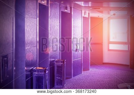 View Of 4 Elevator Doors In A Hotel At Sunset Through A Window. Wide Viewing Angle Of Several Modern