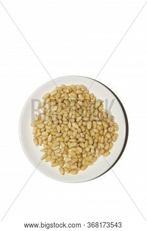 Organic Food. Pine Nuts On A White Background. Cedar Nuts Flatlay On A White Saucer. Agricultural Co