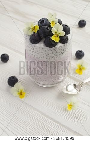 Pudding With Chia,blueberries And Flowers  In The Glass On The White Wooden  Background. Closeup. Lo