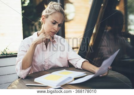 Thoughtful Woman Sitting In Cafe And Analyzing Document