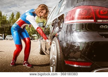 Moscow, Russia - July 06, 2020: Woman Captain America. He Hits The Car And A Dent Remains On It. Gir