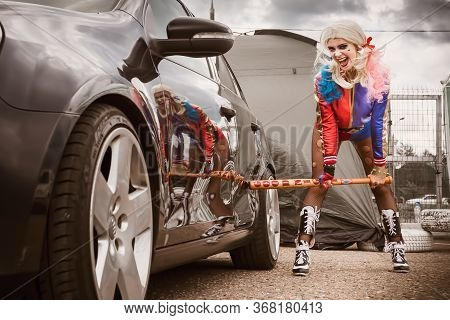 Moscow, Russia - July 06, 2020: Harley Quinn Hits A Parked Black Car With A Baseball Bat. There Is A