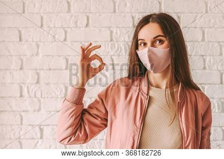 Portrait Happy Woman In Stylish Medical Face Mask Showing Okay Gesture With Hand. Beautiful Millenni