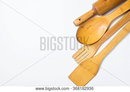 Four Wooden Cutlery Lie In A Row On The Right Side Of The Photograph On A White Background. Wooden S