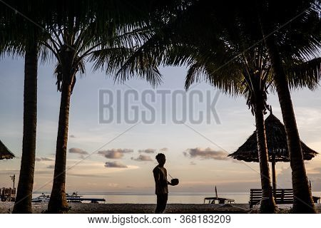 Mabul Island, Sabah, Malaysia - August 08, 2018: The Silhouette Of A Young Man Holding A Coconut In