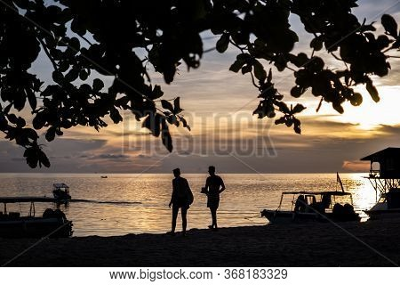 Mabul Island, Sabah, Malaysia - August 08, 2018: The Silhouette Of A Couple Walking In The Beautiful