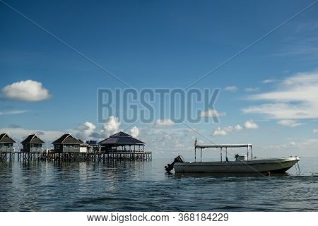 Mabul Island, Sabah, Malaysia - August 08, 2018: A Boot And A Chalet Floating On The Blue Ocean, A F