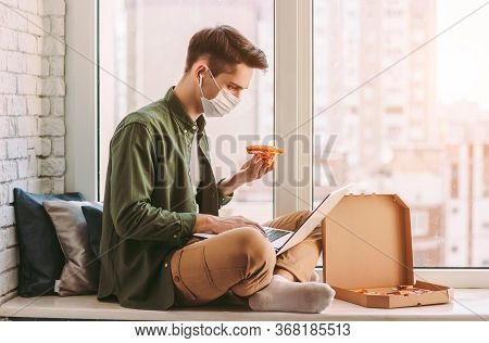 Hungry Businessman In Medical Face Mask Eat Pizza Snack, Use Laptop For Work From Home Office. Styli