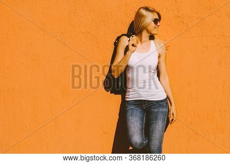 young  smiling blonde woman in white tank top and sunglasses against yellow wall outdoor in city summer heat