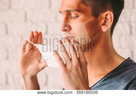 Portrait Young Confused Hipster Man With Funny Sun Tanned Lines On Face Holding Protective Mask In H