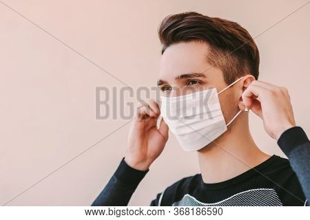 Confident Sports Man In Medical Face Mask Listens Music With Wireless Earphones. Happy Fitness Instr
