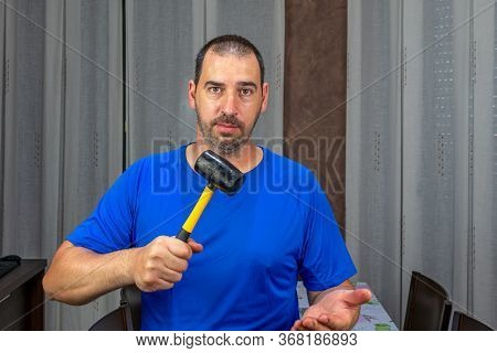 Man With A Beard And Short Hair In A Blue Shirt With A Rubber Hammer In A Defiant Attitude. Fury Con
