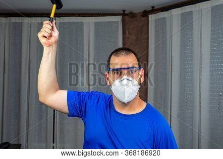 Man With A Beard And Short Hair In A Blue Shirt And A Mask To Prevent Coronavirus With A Rubber Hamm