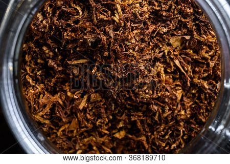 Close-up Macro Cigar And Pile Of Cut Tobacco Leaves Of Dried Tobacco In Glass Jars On Rustic Wood Da