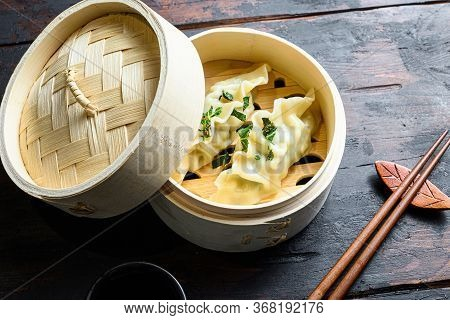 Gyozas Potstickers Chinese Dumplings In Wooden Steamer With Soy Sauce Fresh Herbs And Chopsticks On