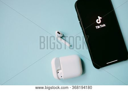 Iphone And Airpods With Tiktok Logo On The Screen, Blue Background. Tiktok Is App To Create And Shar