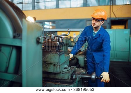 Worker in uniform and helmet works on lathe